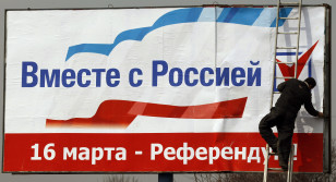 "A worker puts up a poster that reads, ""Together with Russia"" in Simferopol."