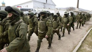 Russian soldiers march through Crimea's capital Simferopol, the day before Crimeans were to vote on joining Russia. Photo: Reuters