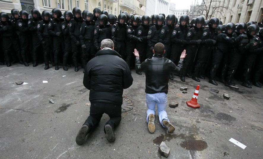 Men kneel down while riot police stand guard near the presidential administration building during a rally held by supporters of EU integration in Kiev