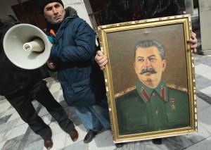 Женщина держит потрет Сталина у дома, в грузинском городе Гори. Десятки грузинских коммунистов собрались здесь 5 марта в 59-ю годовщину его смерти. Фото: Reuters, Давид Мдзинаришвили