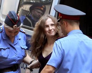Мария Алехина, член женской панк-группы Pussy Riot, под «эскортом» полиции направляется в московский суд 31 июля. Фото: Reuters/Сергей Карпухин