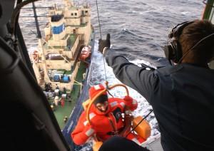 Выжившего при крушении платформы в Охотском море поднимают на борт вертолета со спасательной лодки. Фото: Associated Press