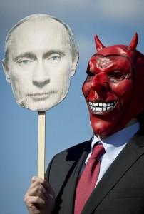 Один из участников акции протеста против путинской кампании в отношении НКО, проходившей во время недавнего посещения российским президентом Ганноверской промышленной ярмарки. За последние недели полиция пришла с «проверками» в московские офисы таких организаций, как Amnesty International и Transparency International. Фото: AFP/Odd Andersen