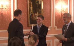 Ужин 9 октября. Томас (бывший сотрудник АНБ) вручает Эдварду Сноудену (экс-АНБ) свечу – символ премии Сэма Адамса, предполагающей освещение темных углов. (Кадр видео WikiLeaks)