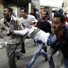 Egyptians carry an injured  protester during clashes with anti-riot police in Cairo, Egypt, Saturday, Jan. 29, 2011. (AP Photo/Ben Curtis)