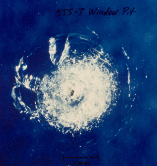 A tiny piece of space junk (a paint fleck) damaged the window of the space shuttle during the STS-7 mission (Photo: NASA Orbital Debris Program Office)