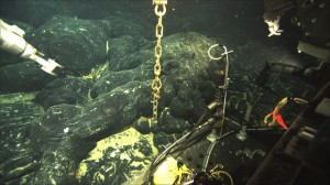 The chain is all that is visible of an ocean-bottom hydrophone buried in about six feet of new lava from an April 2011 eruption of Axial Seamount. (photo courtesy of Bill Chadwick and Bob Dziak of Oregon State University; copyright Woods Hole Oceanographic Institution)