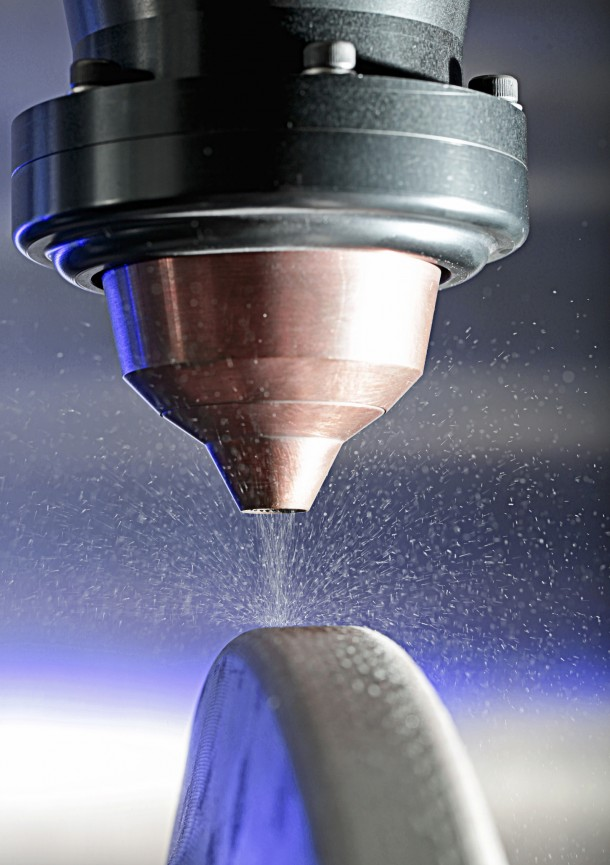 Glassy powder being applied to a metal component, when the powder is fused with lasers it forms a new super durable coating material that helps extended the life of tools that wear out quickly (Photo:Oak Ridge National Laboratory)