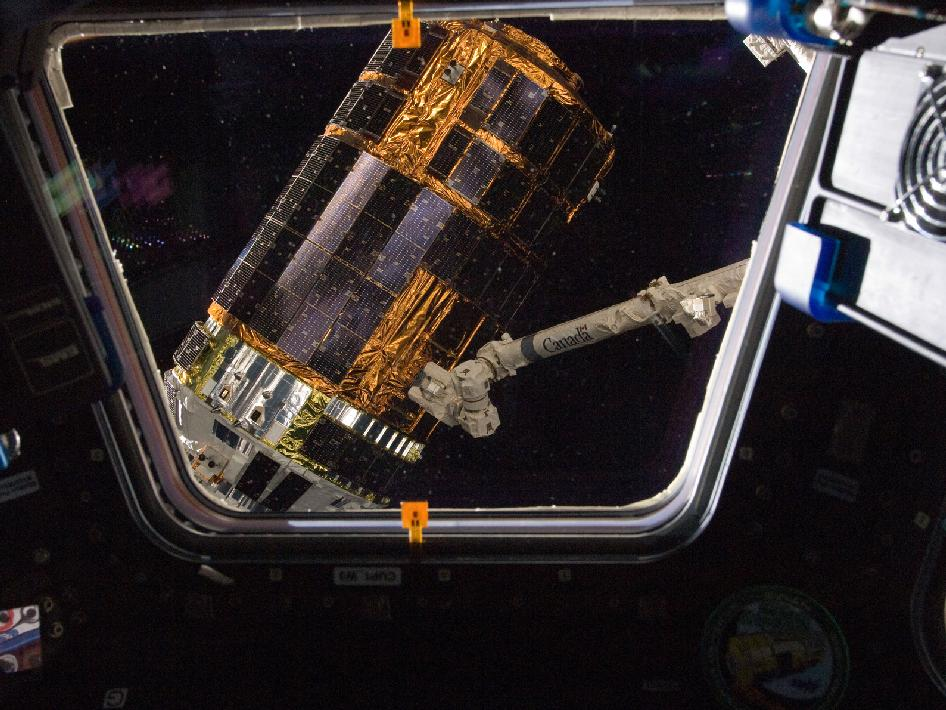 As seen through a window in the Cupola, the International Space Station's Canadarm2 grapples the unpiloted Japan Aerospace Exploration Agency (JAXA) H-II Transfer Vehicle (HTV-3) (Photo: NASA)