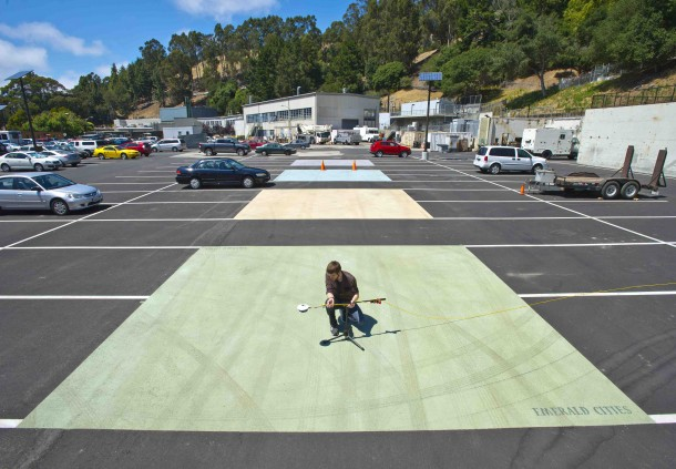 The Heat Island Group at Lawrence Berkeley National Laboratory works to cool buildings, cities, and the planet by making roofs, pavements, and cars cooler in the sun.  Here, Jordan Woods takes measurements of new cool pavement coating using a device albedometer. Other sample pavement coatings can be seen behind him. (Photo: Lawrence Berkeley National Laboratory)