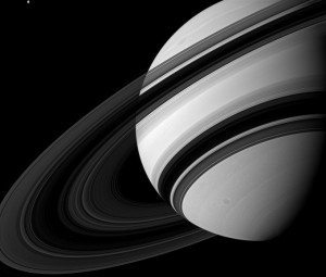 The moon Tethys (in the upper left of the image) is seen next to Saturn in this NASA image taken from the Cassini spacecraft on Aug. 19, 2012 and released Dec. 3, 2012. Saturn's rings appear to dwarf Tethys (660 miles, or 1,062 kilometers across) although scientists believe the moon to be many times more massive than the entire ring system combined. The view was acquired at a distance of approximately 1.5 million miles (2.4 million kilometers) from Saturn. (REUTERS/NASA)