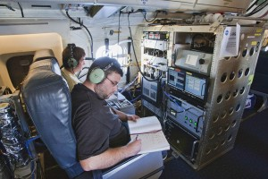 Terry Lathem, a graduate student in Georgia Tech's School of Earth and Atmospheric Sciences, takes notes aboard a NASA DC-8 aircraft gathering samples of microorganisms in the atmosphere. (Photo: NASA)