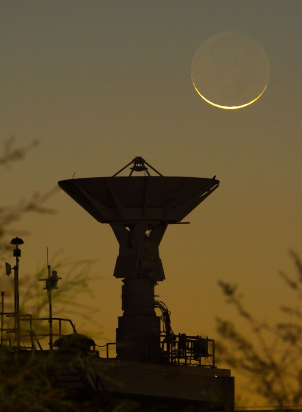A crescent moon and NASA's Johnson Space Center's S-band dish, atop Building 44. (Photo: NASA/Mark Sowa)