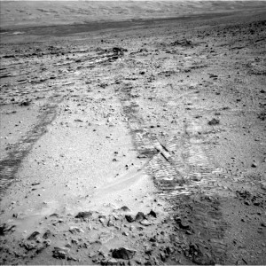 "This view from the left Navigation Camera (Navcam) of NASA's Mars Rover Curiosity looks back at wheel tracks made during the first drive away from the last science target in the ""Glenelg"" area. The drive commenced a long trek toward the mission's long-term destination: Mount Sharp.  (NASA/JPL/MSL)"