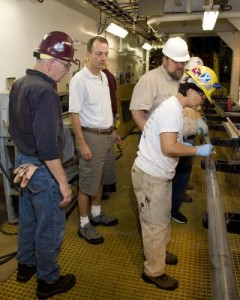 Research leader Will Sager (white polo shirt) waits with technicians to inspect a core sample drilled from the Shatsky Rise Formation. (IODProgram/USIO)