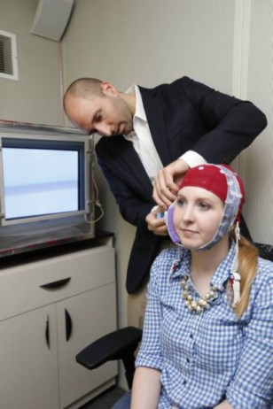 Robert Reinhart applies the electrical stimulus to subject Laura McClenahan. (John Russell/Vanderbilt University)