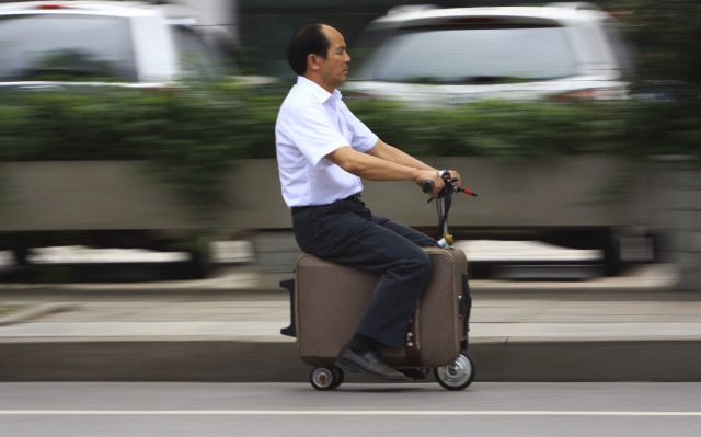 He Liang spent 10 years transforming an ordinary suitcase into an electric powered motor scooter.  He's shown here riding his home-made suitcase-scooter down a street in Changsha, Hunan province.   He Liang says that the suitcase-scooter can zoom down the road at a top speed of up to 20km/h and one electrical charge will allow it to travel up to 50-60km. (Reuters)
