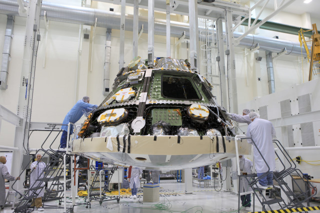 NASA engineers finish their installation of the Orion spacecraft's heat shield.  The heat shield will help protect those who ride back to Earth aboard the Orion from the blazing hot temperatures – about 2,205° Celsius - it will endure during its reentry into Earth's atmosphere. June 5, 2014 (NASA)