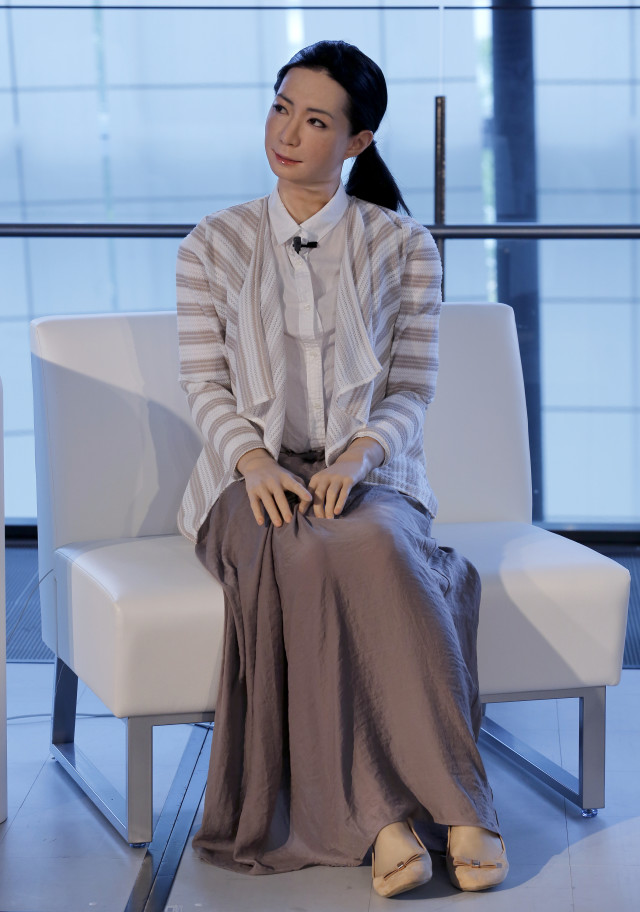 Otonaroid, a female-announcer robot is shown here addressing a crowd during a press event at the National Museum of Emerging Science and Innovation Miraikan in Tokyo Tuesday, June 24, 2014. Android expert Hiroshi Ishiguro, who created Otonaroid, also demonstrated others that included another girl robot called Kodomoroid and a bald-headed mannequin robot with pointed arms called Telenoid. (AP)