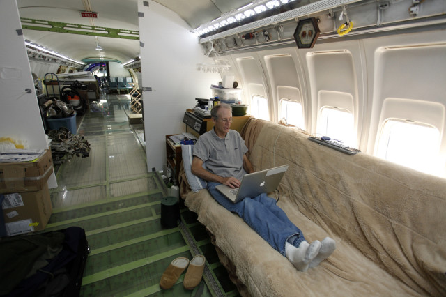 Bruce Campbell sits on his futon bed while using a laptop in his Boeing 727 home in the woods outside the suburbs of Portland, Oregon