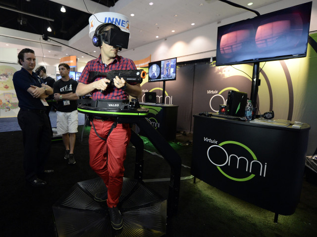 An attendee tries out the Virtuix Oculus Rift and Omni Treadmill game at the 2014 Electronic Entertainment Expo, known as E3, in Los Angeles