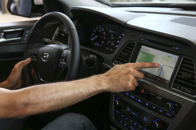 A Google employee demonstrates the Android Auto interface at the Google I/O developer's conference in San Francisco June 26, 2014. An Android powered device will interface with the auto's dashboard touchscreen system to provide drivers with a safe way to access and operate Android's built-in navigation, communication and entertainment applications by just using voice commands. (Reuters)