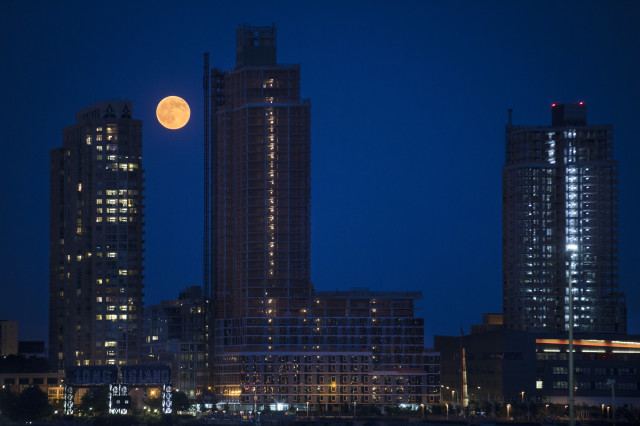 "On Saturday, July 12, 2014 the world was treated to a remarkable sight in the night sky; a ""supermoon"".  Also called a perigee moon, it's shown here rising over the Queens borough of New York.  Scientists say that a ""supermoon"" takes place when the moon is close to the horizon, making it appear larger and much brighter than other ""regular"" full moons. (AP)"