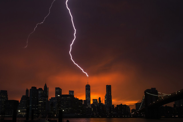 With the sun setting over New York on July 2, 2014, the One World Trade Center building in Manhattan is struck by lightning during a summer storm.  (REUTERS)