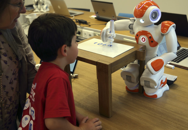 "A child looks at a humanoid robot named ""Nao"" as it does some math calculations at the workshop of Aldebaran Robotics Company located in Issy-Les-Moulineaux near Paris on July 2, 2014. The workshop allows the public to meet and interact with humanoid robots like Nao. (Reuters)"