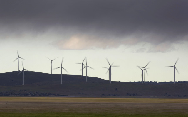 Low rain clouds are shown here passing over a group of wind turbines at the Capital Wind Farm near Tarago, Australia on July 9, 2014. (REUTERS)
