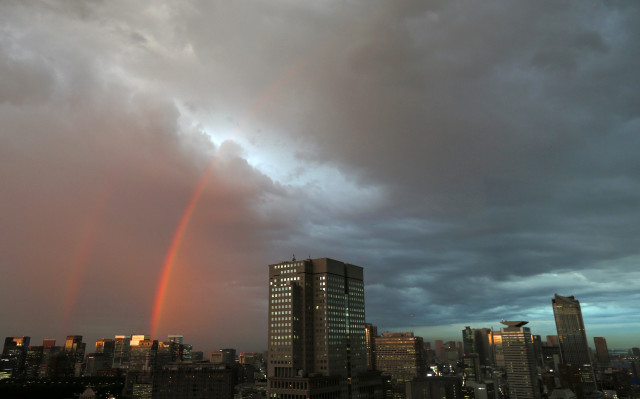 Residents of Tokyo are reassured by twin rainbows that appeared at sunset, July 11, 2014, over city skyscrapers after Typhoon Neoguri passed through the region (Reuters)