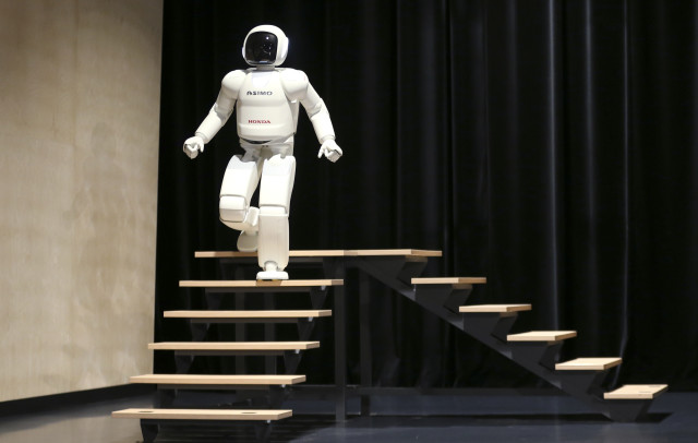 Taking a leisurely stroll down a set of stairs is the latest version of Honda's Asimo humanoid robot.  With enhanced intelligence and more nimble hand dexterity, the new robot was introduced to the public at an exhibition held near Brussels on July 16, 2014.  (Reuters)
