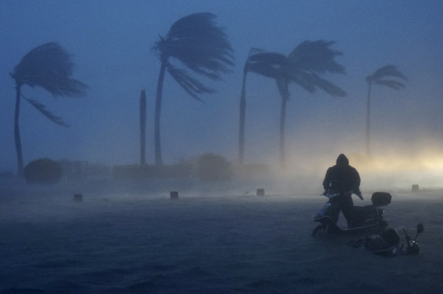 Never question the power of Mother Nature – the violent typhoon Rammasun hit the city of Haikou, in China's Hainan province on July 18, 2014.  Here you see a resident of the city as he pushes his electric bicycle through a flooded seaside street against the storm's strong wind and heavy rainfalls.  (Reuters)