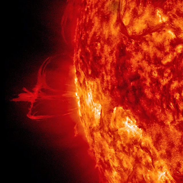 NASA released this photo on August 6, 2014, that shows a thin solar prominence above the Sun.  The prominence, which is controlled by the sun's strong magnetic fields beneath it, then sprouted a number of plasma streams that disappeared back into the sun about a day later. NASA said that the photo was taken in extreme ultraviolet light. (NASA/SDO)