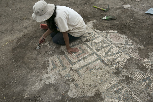 A student of archeology uses her trowel to remove dirt from an ancient mosaic floor that was discovered at an excavation site in Kosovo's ancient city of Ulpiana, on August, 21, 2014.  The archeologists exploring the site have discovered a baptistery that they believe to dates back to the 4th century AD. (AP)