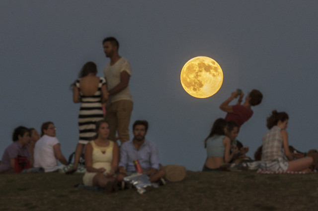 Gathering in a Madrid park, people enjoy the spectacular sight of a perigee moon, also known as a supermoon, as it rises above them on Sunday, Aug. 10, 2014. A supermoon takes place when the moon is near the horizon and appears larger and brighter than other full moons. (AP)