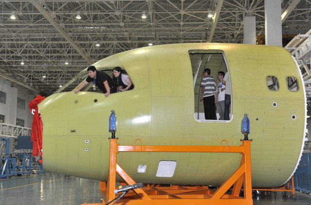 Curious visitors, on July 31, 2014, check out the nose/cockpit area of China's new C919 airliner that's currently being built in the Sichuan province.  The nose portion of the airliner, that being built by the Commercial Aircraft Corporation of China is the second significant piece of the C919 to be completed. (Reuters)