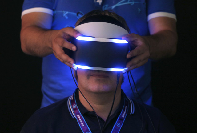 "A man attending Gamescom 2014, Europe's largest video games trade show, is shown here trying on Sony's ""Project Morpheus"" virtual reality headset.  Gamescom 2014 runs through Sunday, August 17, 2014 in Cologne, Germany.  (Reuters)"