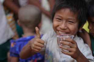 Child quenches thirst with some water (USAID)