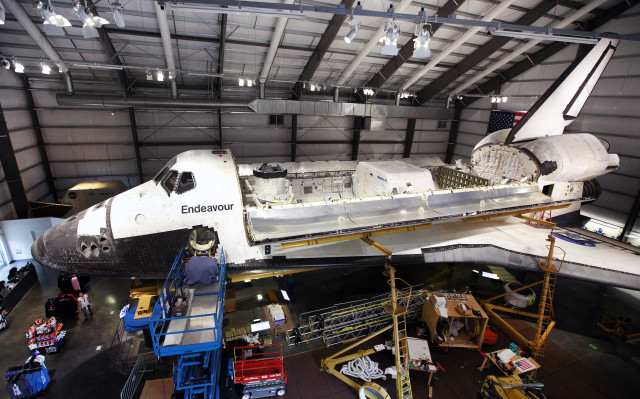 The bay doors of the space shuttle Endeavour are shown wide open following the installation of a space lab, storage pod, replica robotic arm and docking system on 10/10/14.  After being retired following its final mission on 3/9/11, the Endeavor is now being kept at the California Science Center in Los Angeles. (AP)