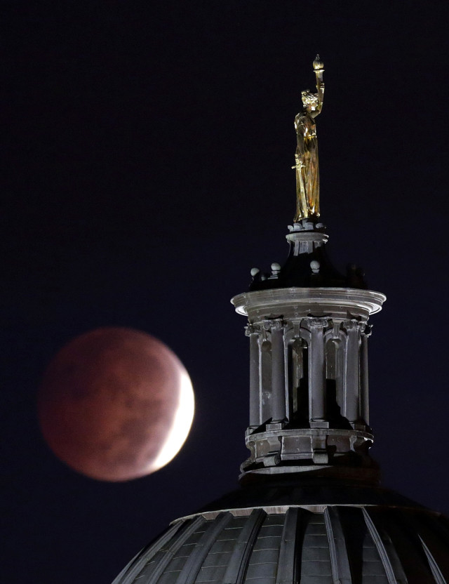 "The 10/8/14 lunar eclipse is can be seen behind a statue entitled ""Enlightenment Giving Power"" by John Gelert.  The statue sits atop the dome of the Bergen County Courthouse in Hackensack, N.J.  (AP)"