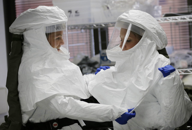 Two members of the US Department of Defense's Ebola Military Medical Support Team are seen here, on 10/24/14, helping each other with the protective gear they wore during training at San Antonio Military Medical Center in San Antonio. (AP)