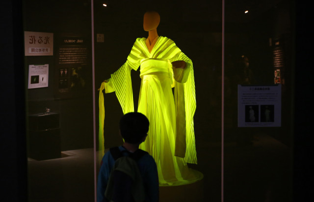 "A boy visiting Tokyo's ""Hikari the Wonder of Light"" exhibition on 10/29/14 is seen here looking at a kimono, made from silkworm cocoons, that glow yellow when it's exposed to blue LEDs. (Reuters)"