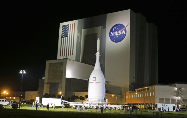 The Orion Spacecraft moves past NASA's Vehicle Assembly Building on November 11, 2014, as it slowly makes its 22 mile journey from the Launch Abort System Facility at the Kennedy Space Center in Cape Canaveral, Fla.  Orion is scheduled to launch for a test flight on Dec. 4, 2014. (AP)