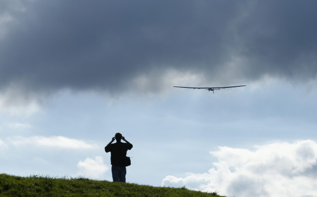A man watches a test flight of the solar-powered Solar Impulse 2 experimental aircraft, piloted by Swiss Bertrand Piccard, in Payerne November 13, 2014.  An attempt to fly around the world in stages using only solar energy will be made in 2015. (Reuters)