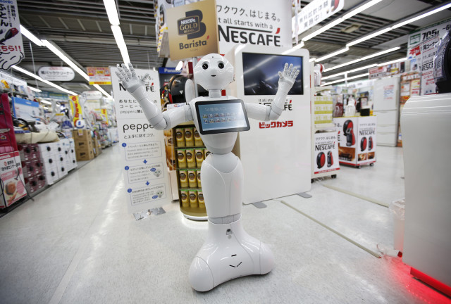 """Pepper"", a friendly human-like robot is shown here at its new job selling new Nestle coffee machines at a Tokyo electric shop on 12/1/14.  Nestle says it would like to have robots like ""Pepper"" working at 1,000 stores by the end of next year.  (Reuters)"
