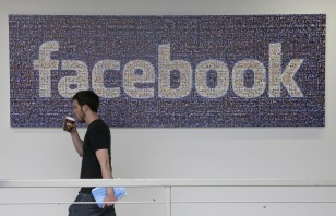 FILE - Facebook employee walks past a sign at company headquarters in Menlo Park, California. (AP)