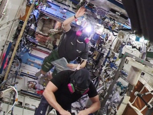 Astronauts Barry WiImore (foreground) and Terry Virts re-entered the U.S. segment wearing protective masks.  (NASA TV)
