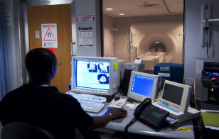 A technician watches as patient enters a Magnetic Resonance Imaging, (MRI) machine at the National Naval Medical Center in Bethesda, Maryland. (U.S.Navy/Wikimedia Commons)
