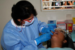Dentist conducts dental exam on a patient (US Army, 807th Medical Command)